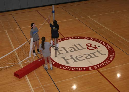 JEWEL DEVORAWOOD | the broadview. JV volleyball team sets up the net next to the
