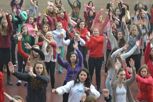 Junior Dani Hogan and freshman Corinne Sigmund (center) dance with the student body as a part of the One Billion Rising movement today. The V-Day event raised awareness for abuse against women.