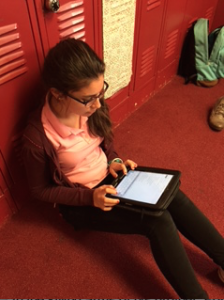 Freshman Carlota Rubio reviews her poem after she submitted it.