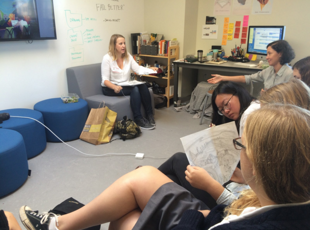 Students+examine+drafts+of+Bryana+Fleming%27s+murals+as+she+speaks+about+her+process+for+creating+art.