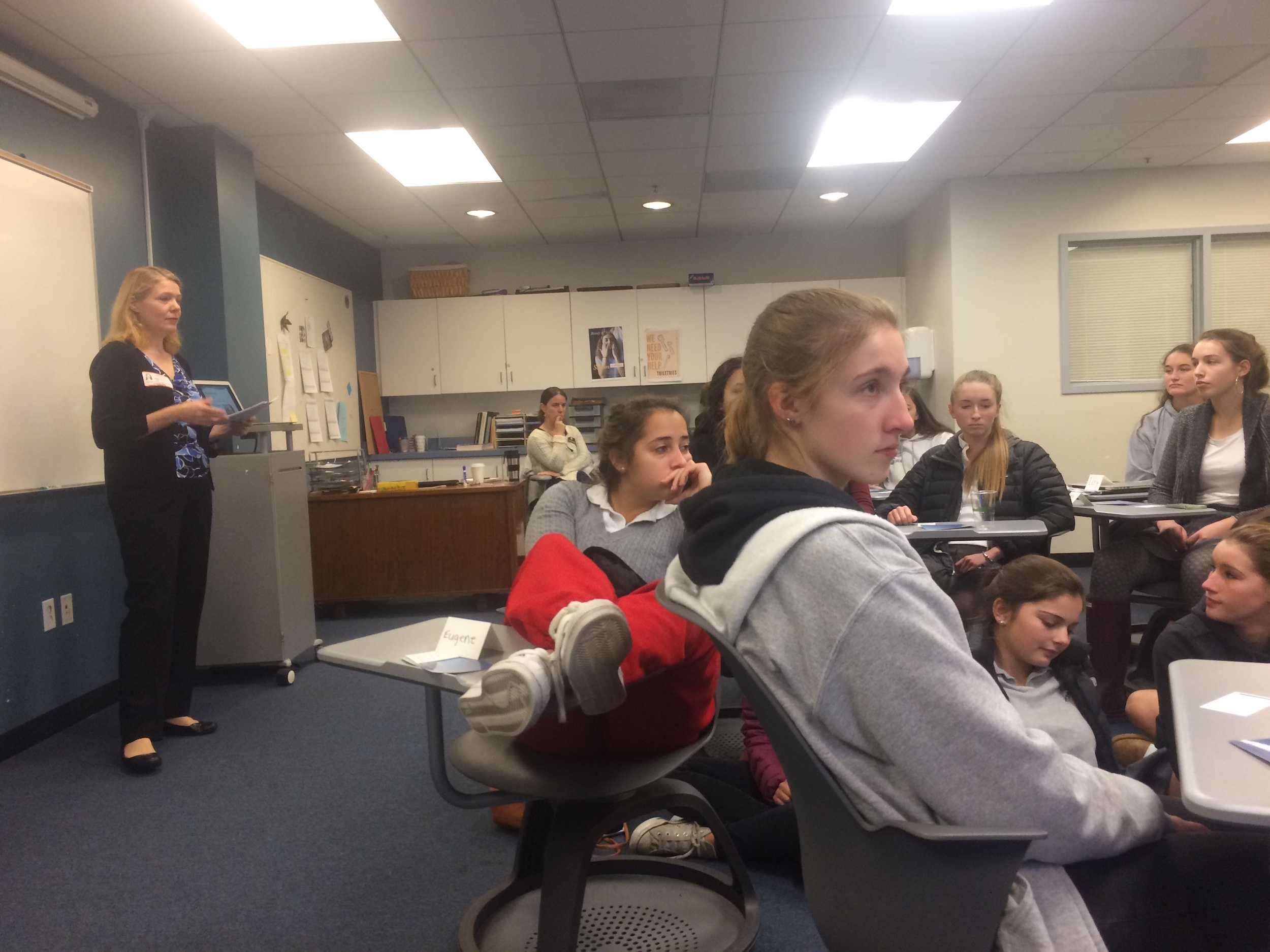 Attendees listen to Dummel as they view her presentation listing stress reduction methods. Juniors and seniors also did breathing exercises and meditation in order to bring the stress reduction process to life.