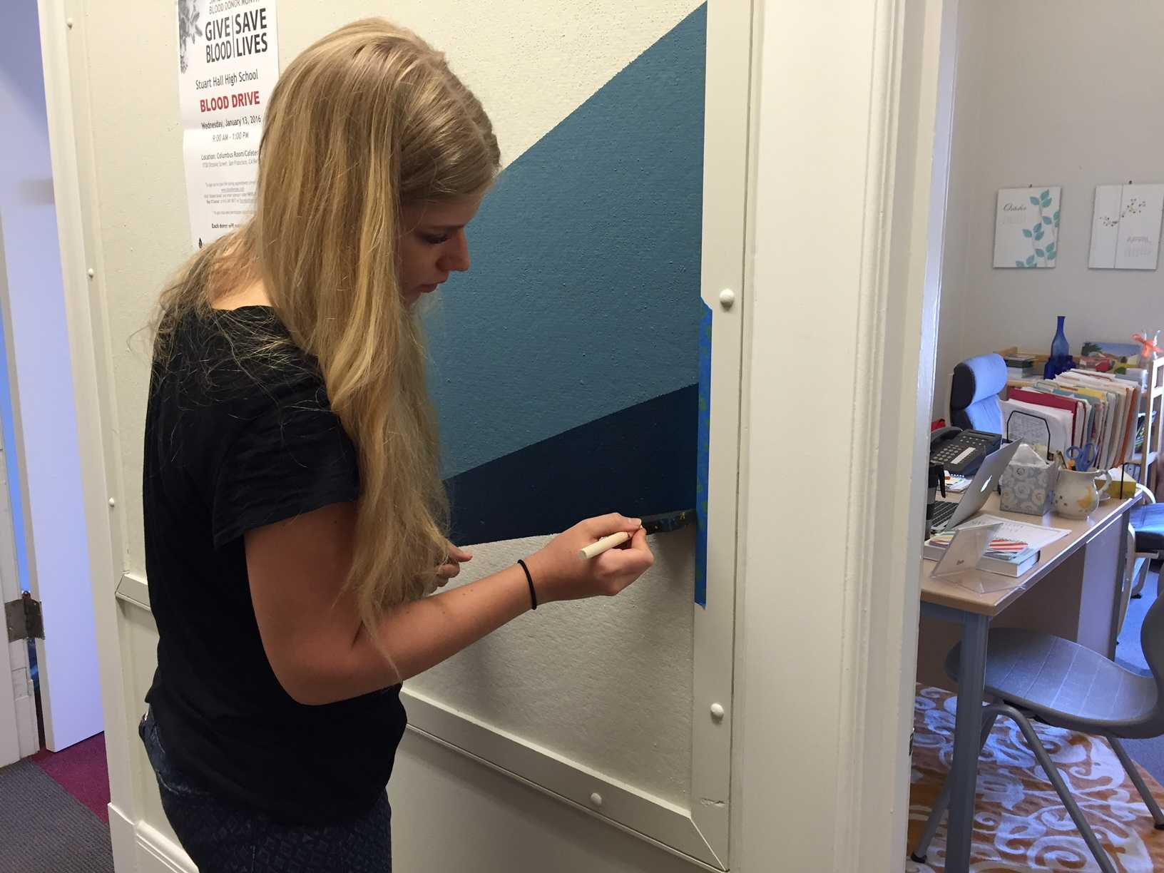 Alumna Sabine Kelly ('15) touches up part of the mural on the third floor near the faculty room. The doors in front of the hallway were removed before the painting of the new mural.
