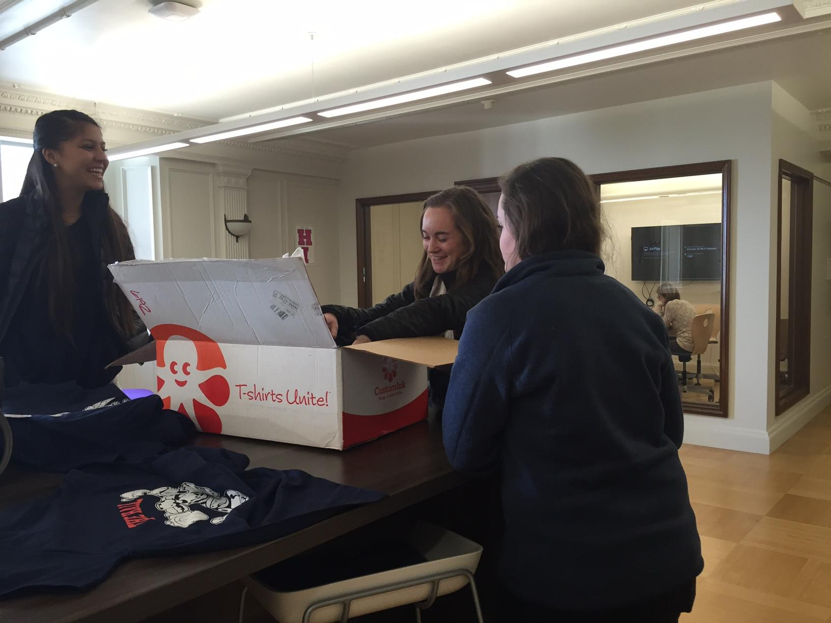 Student Body Publicity Director Victoria Oysterman and Student Body Secretary Nora Hanak sell a shirt to senior Sarah McCarthy. The shirts raise awareness for the upcoming Stuart Hall High School varsity basketball game tomorrow night.