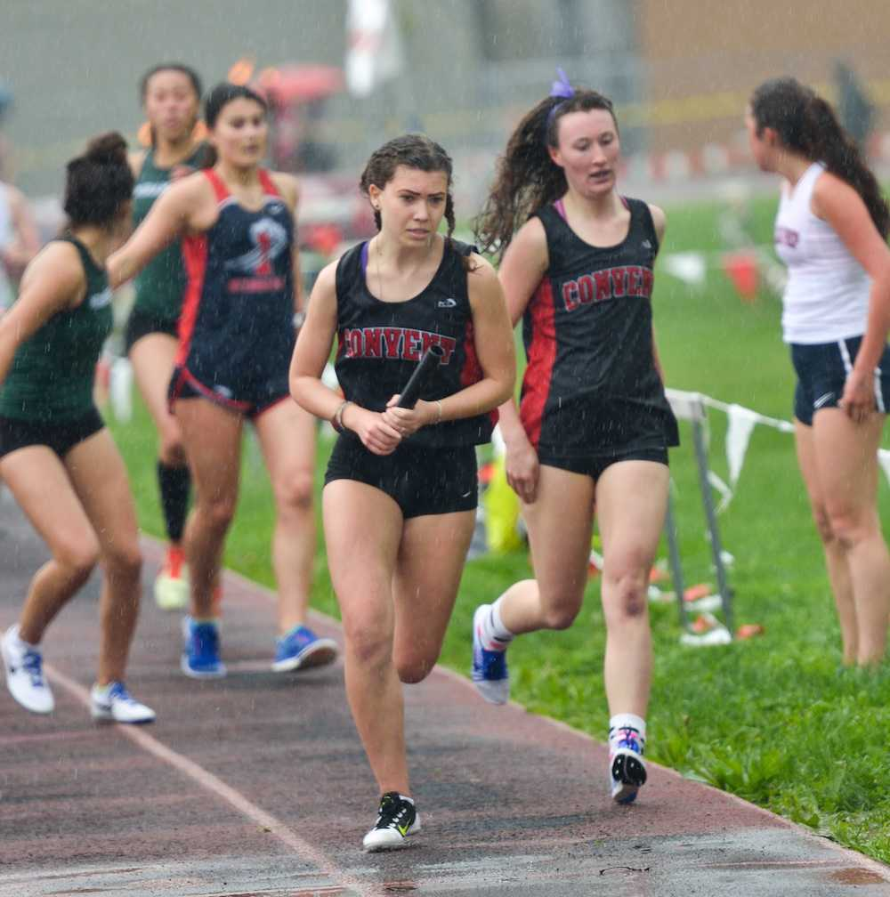 Five girls beat their personal bests. Junior Ana Cahuas receives the baton from senior Mae Singer while racing in the rain.