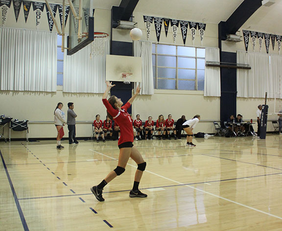 Sophomore Avery Van Natta eyes the ball in the air as she prepares to serve it over the net. Varsity volleyball fell short against Urban in its first league game, losing two sets to three.
