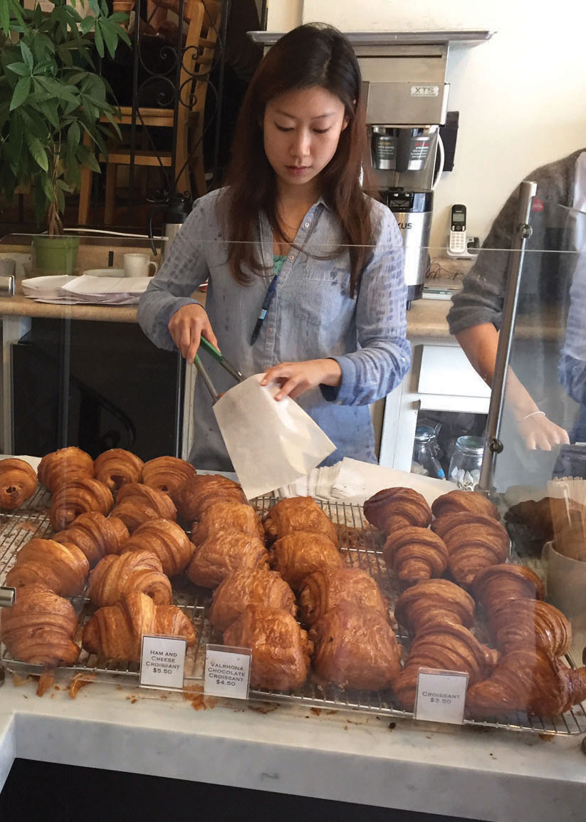 An Arsicault Bakery employee prepares croissants for patrons. Plain, savory and sweet croissants range from $3.50 to $5.50.
