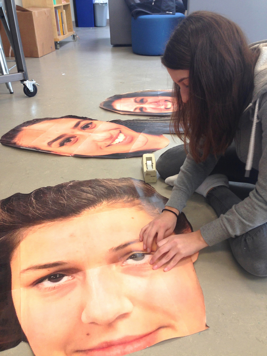Varsity basketball player Kiki Apple finishes posters, each the face of a senior on the team, for Senior Night in the art room. The posters were hung next to each player's name and number in the gym.