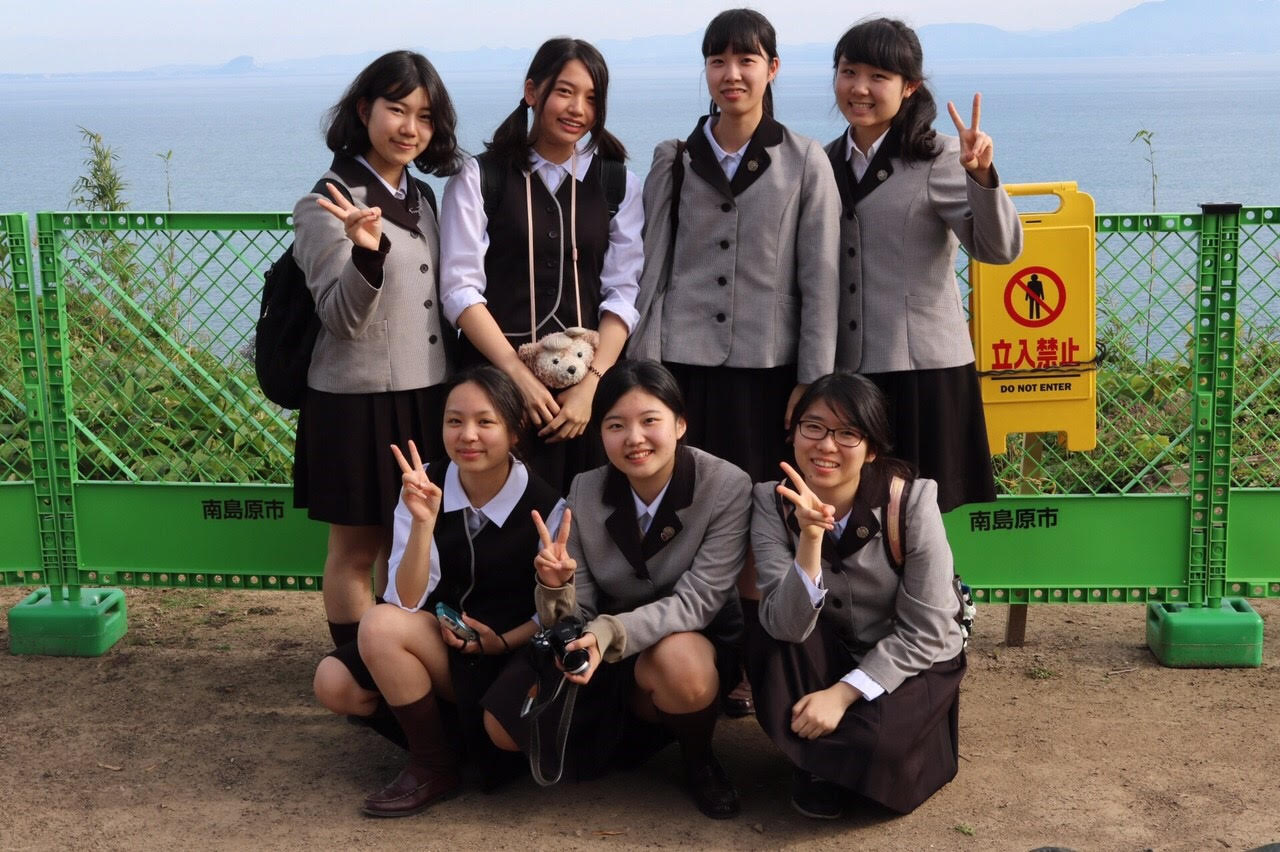 High school third graders, the equivalent of a high school senior in the United States, from Sapporo Sacred Heart School in Japan pose in their winter school uniforms. The uniform varies seasonally, with a brown checked skirt and blouse in summer, and the same skirt with a sweater and hooded jacket and winter.