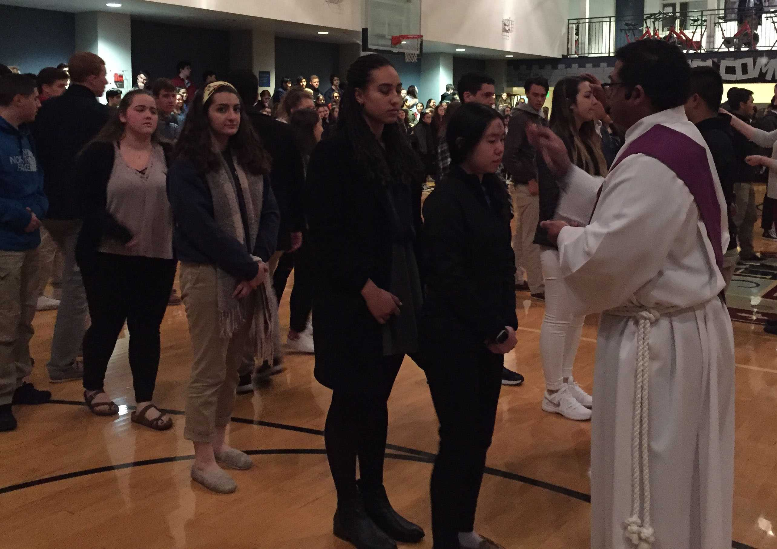 Senior Sarah Hong receives ashes from celebrant Eddy Gutierrez in  The Dungeon. Convent students were transported to Stuart Hall on school buses.