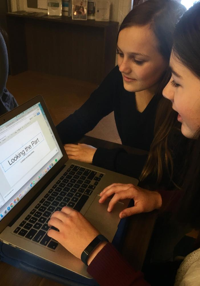 """Sophomores Sophie Mack and Josephine Rozzelle add finishing touches to their TED Talk-style presentation, """"Looking the Part."""" Mack and Rozzelle, who are also in a group with Jordan Russell, focused their project on lookism, a form of oppression that discriminates based off an individual's physical appearance."""