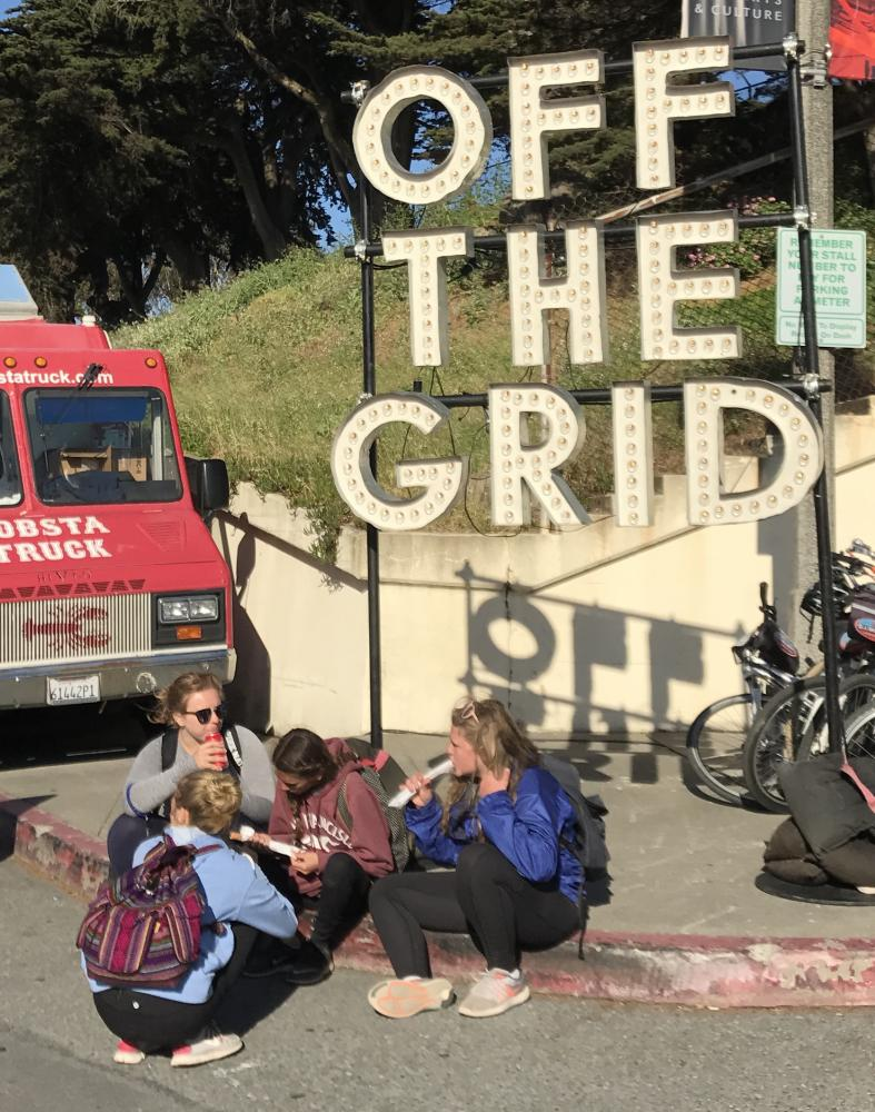 A group of girls eat churros from a nearby food truck while sitting in front of the Off the Grid sign. Off the Grid occurs at Fort Mason every Friday from 5-10 pm.