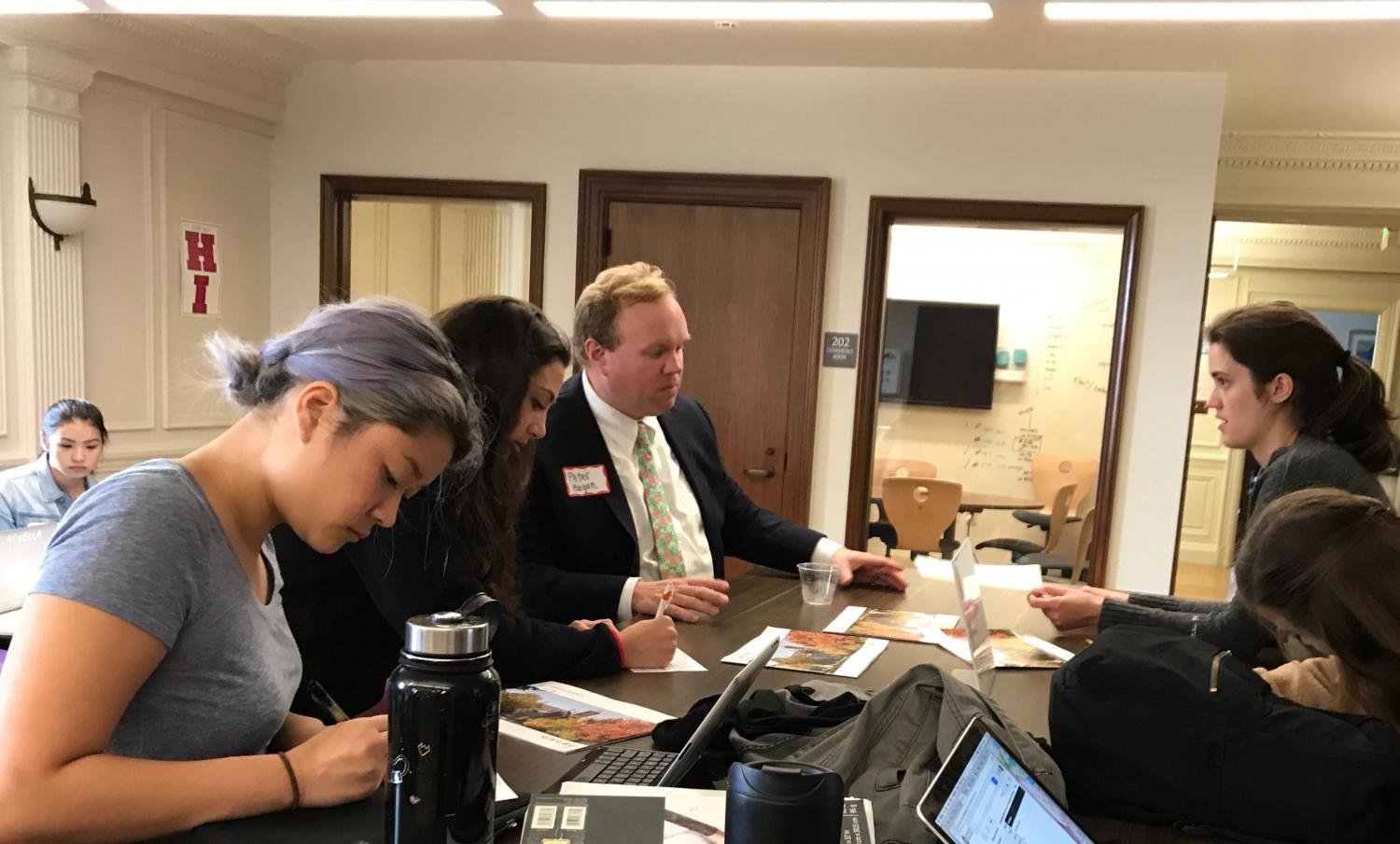 Seniors Marguerite Williamson (right) talks to Syracuse University representative Peter Hagan (center) while Sinead McKeon (right) and juniors Darren Loy and Sofia Pirri (left) fill out papers. Hagan was the first representative to visit this school year.