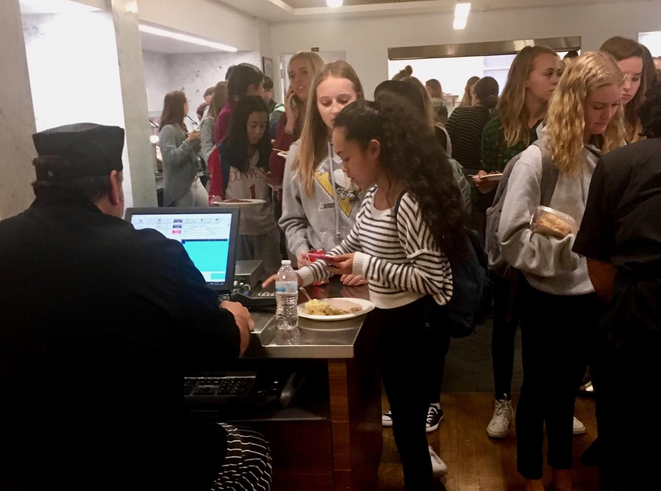 Students wait to pay for lunch as freshmen Aliza Manayan and Hallie Williams enter their pins one at a time. New registers and keypads were introduced along with Sage Dining service this fall.