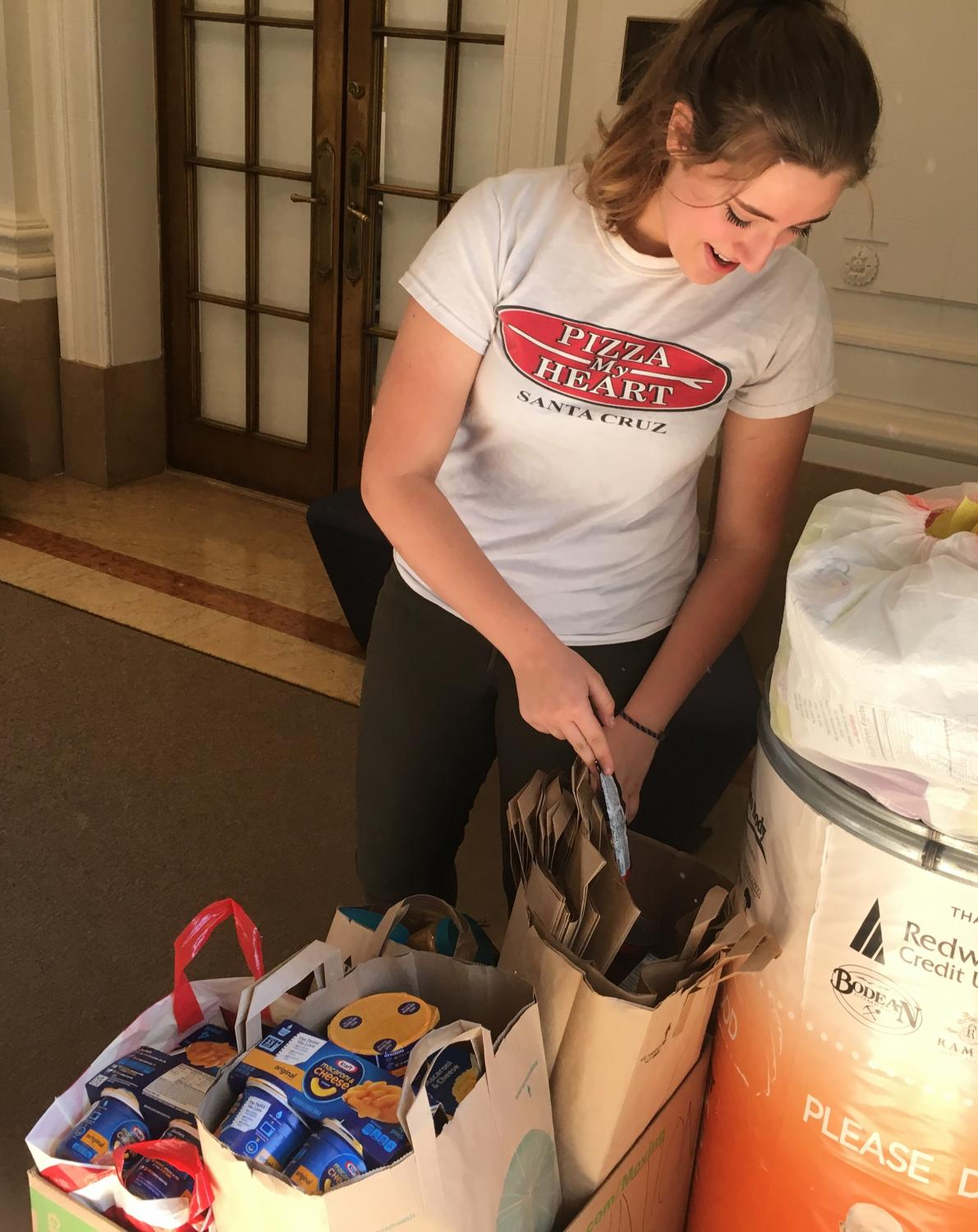 Junior Caroline Phillipps puts food into a donation bin for victims of the North Bay fire. The drive, which started Monday, ends today.