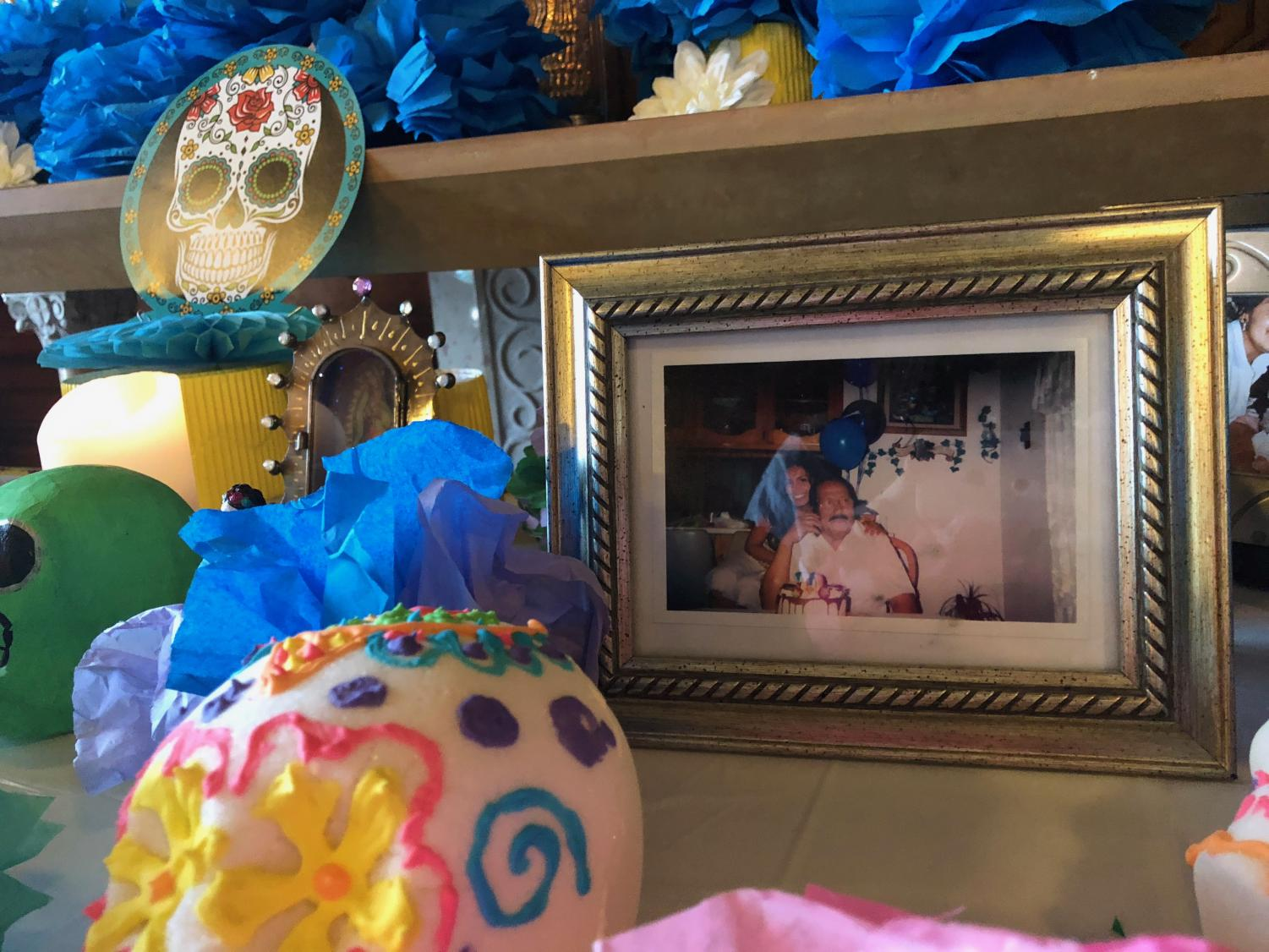 Sophomore Malinali Cervantes leaves a photo of her deceased grandfather on the Dia de los Muertos altar in the chapel. Students and faculty were invited to place an item on the altar in remembrance of loved ones that have died.