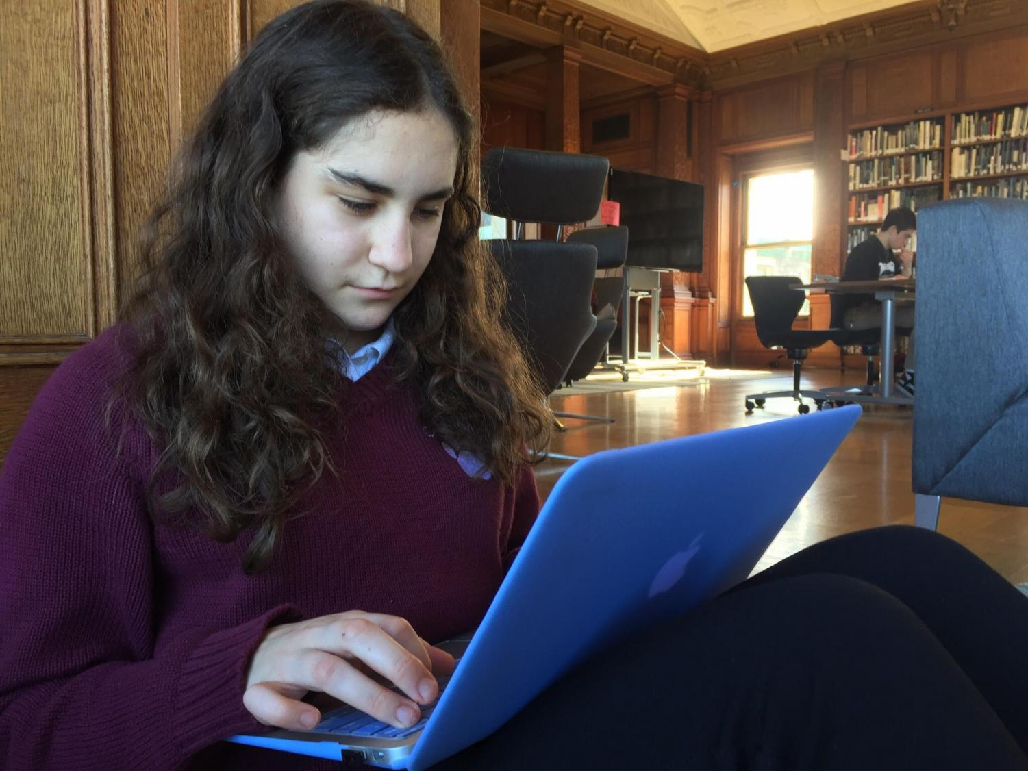 Sophomore Estie Seligman works in the library while wearing full dress uniform. This version of the uniform includes a choice of black slacks or the appropriate skirt with black tights.