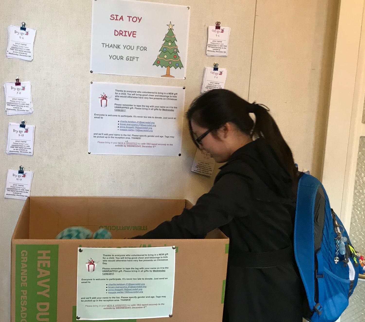 Sophomore and SIA member Michelle Wang sorts through toys in the SIA Christmas toy drive donation bin. The toy drive will continue through Dec. 6.