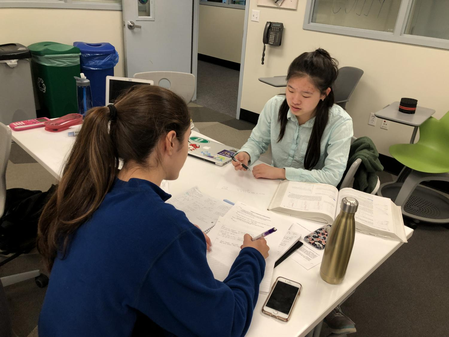 Senior Halie Kim helps senior Guilia Oltranti during peer tutoring session. The students in the room worked with each other as well as with Kim during the tutoring session.