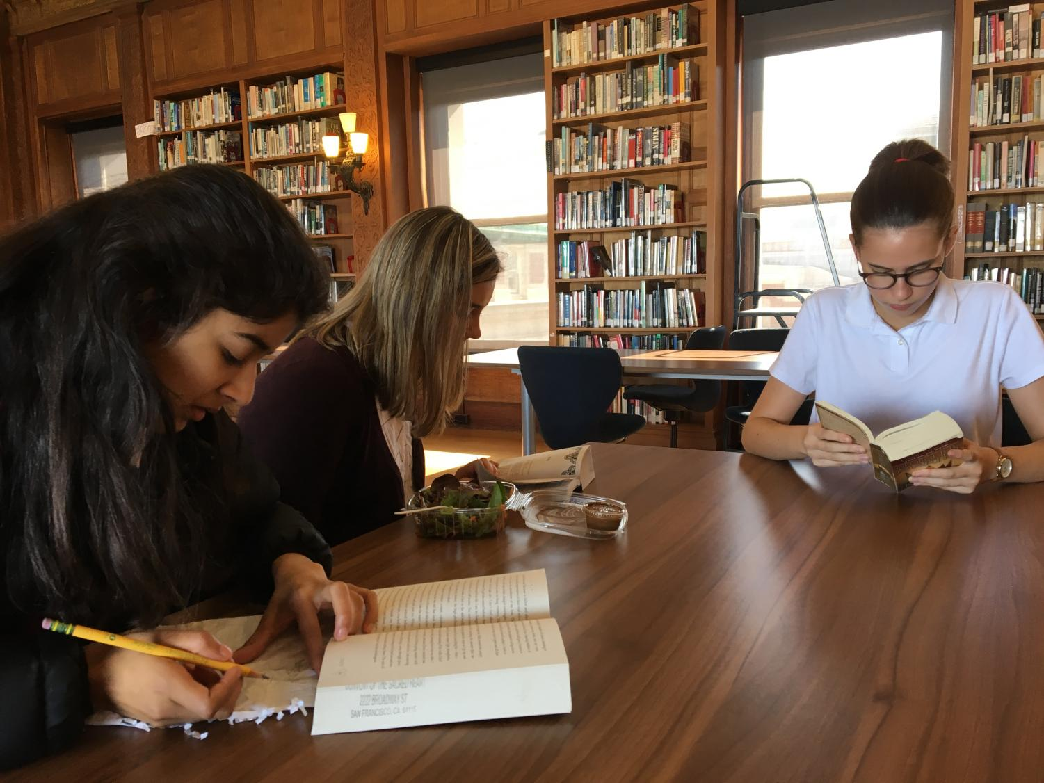 Sophomores Alisha Kalra, Brooke Wilson and Arlena Jackson read in the Mother Williams Library during a book club meeting. The club meets every other Wednesday during lunch.