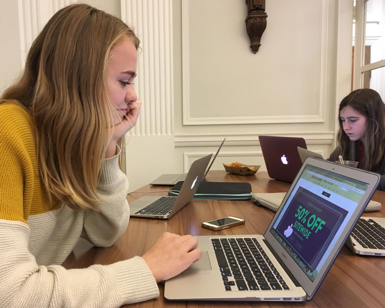 Freshman Sarah Barnes browses a 50 percent off Cyber Monday sale on the PacSun website. Shopping holidays began on Thanksgiving and end with Cyber Monday.