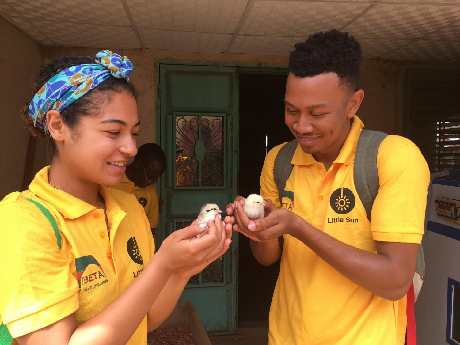 Alumna Bianka Quintanilla-Whye and teammate Paul Watkins hold newly-born chicks hatched in poultry farmer Boureima Kabre's traditionally-powered incubator in Burkina Faso. Their team from Stanford University worked in Kabre's shop assembling a solar powered incubator they designed.