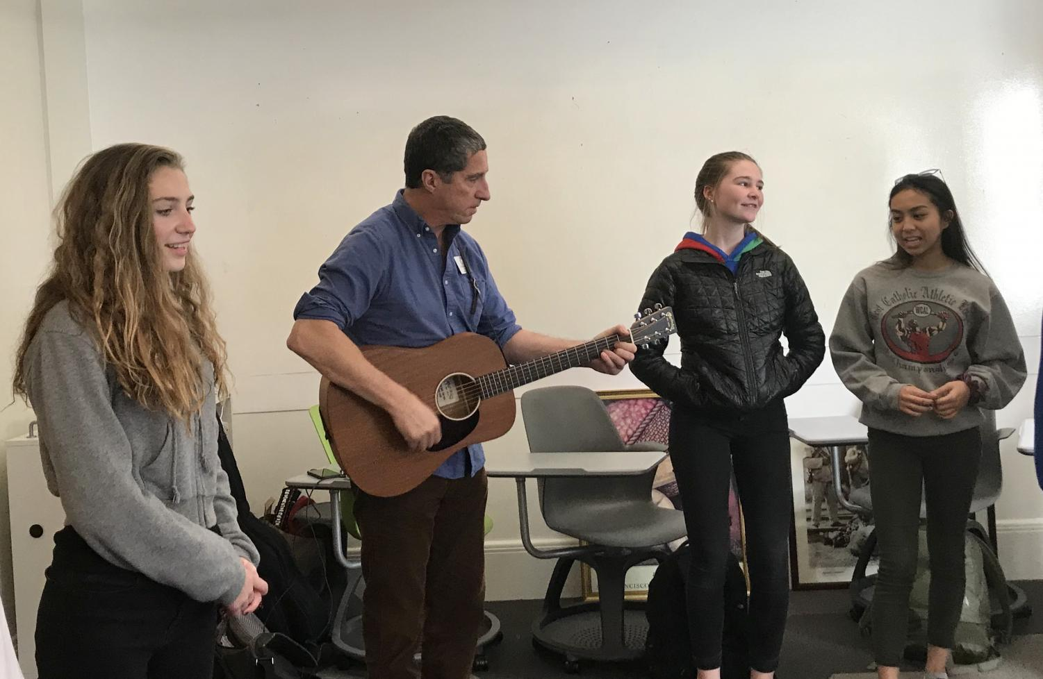 French and Spanish teacher Pascal Parra practices a song with his students from his French II class. The French classes picked a new song this year.