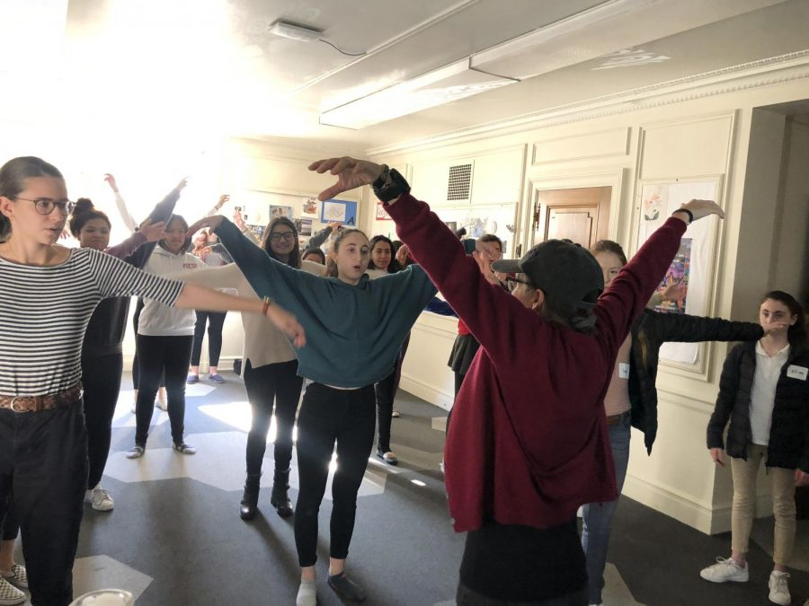 Theology+teacher+Katherine+McMichael+leads+her+sophomores+through+a+QiGong+movement.+The+practice+focused+on+taking+energy+from+the+five+elements+on+Earth%2C+and+is+said+to+allow+energy+to+flow+through+the+body.+