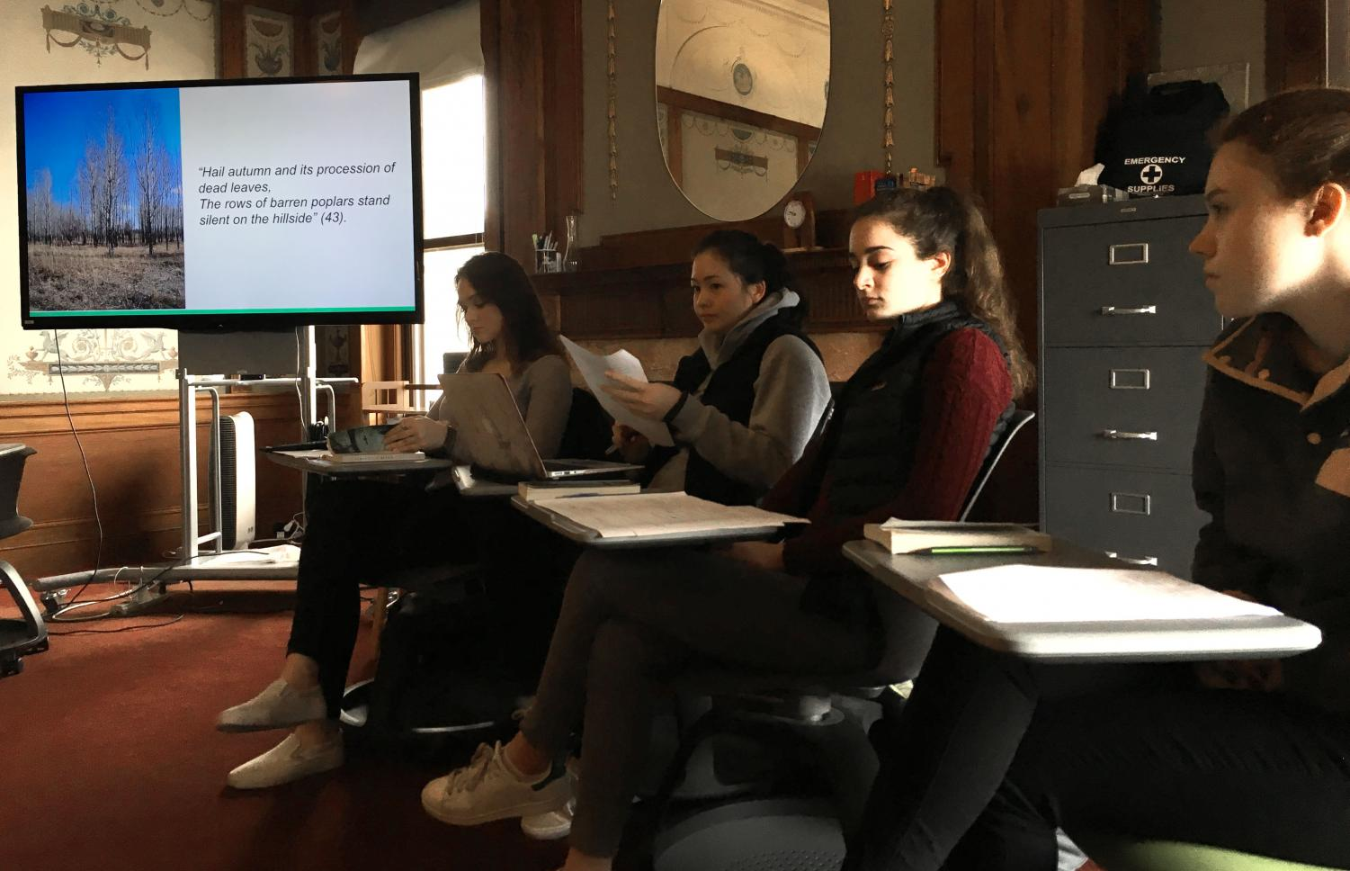 Juniors Hannah Kelliher, Mason Cooney, Emily Kanellos and Laura Mogannam (left to right) analyze a quote during their Interactive Oral Presentation. Their topic explored the significance of music and food in Vietnam, focusing on the novel