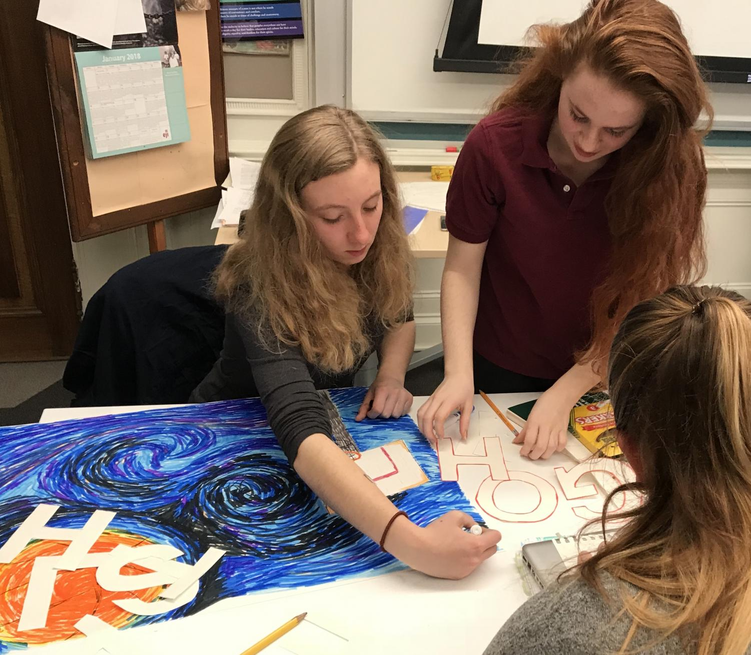 Senior Sydney O'Neil colors a poster in her AP Art History class that will be used to support the Stuart Hall Knights in their basketball championship game. The poster will read 'Van Gough.'