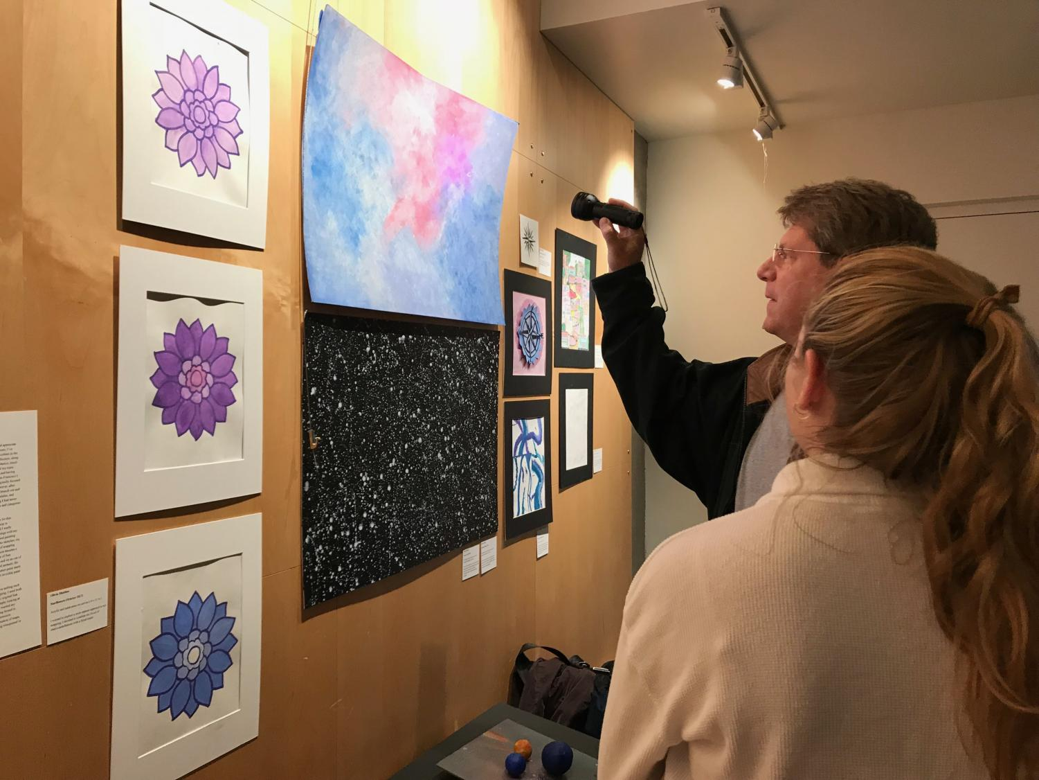 Students and parents explore Olivia Matthes' art pieces during the exhibition. Along with Matthes, many students incorporated an interactive aspect to their pieces — including shining light, music and turning pages.