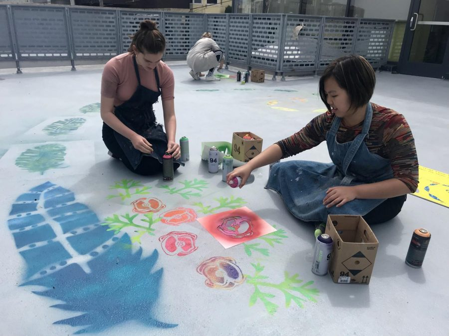 Sophomores+Cat+Webb-Purkis+and+Abby+Widjanarko+spray+paint+California+poppies+and+bald+eagle+feathers+on+the+art+terrance+floor.+The+mural+incorporates+all+elements+of+STEAM.++
