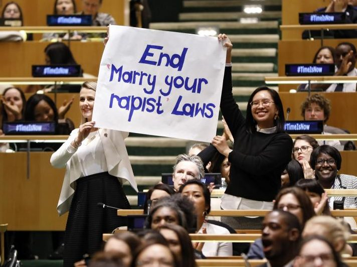 Joëlle Santos '09, right, holds up a sign at the International Women's Day celebration. Other U.N. Women raised awareness for movements such as #MeToo and #TimesUp.