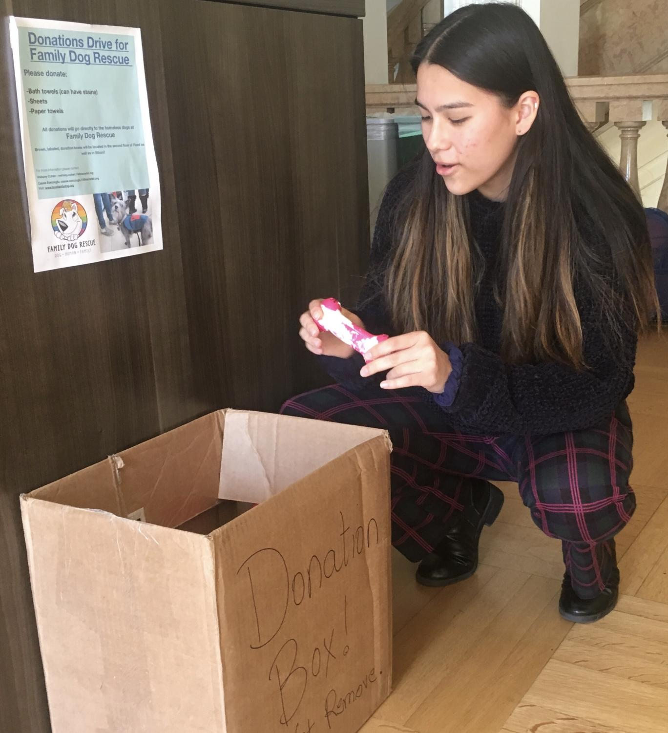Junior Kira Daley donates a dog toy to the Family Dog Rescue drive. There are boxes placed in the Center, Gallery and 2nd floors' Siboni hallway.