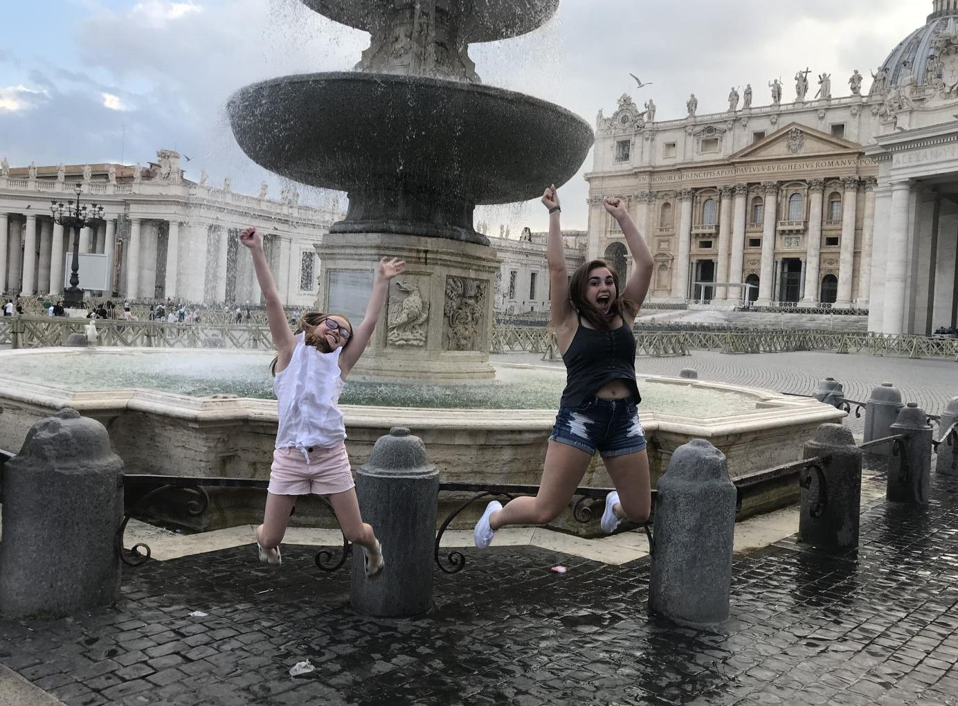 Senior Megan Mullins jumps with her sister in front of the Fountains of St. Peters Square in Italy in June. Students shared their summer experiences, ranging from vacation to summer school.