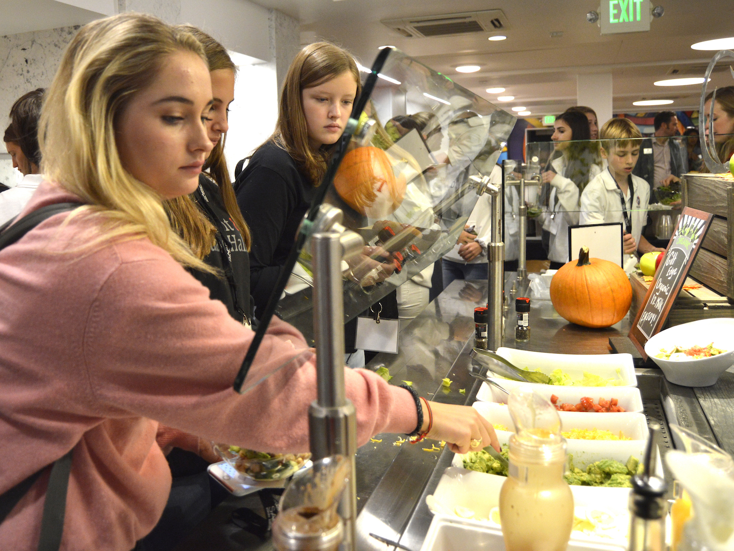 Senior Caroline Schulberg adds avocado chunks and other toppings to her salad from the cafeteria's build-your-own salad bar. Students wear lanyards with their name and photo on them to show that they have paid for the meal plan.