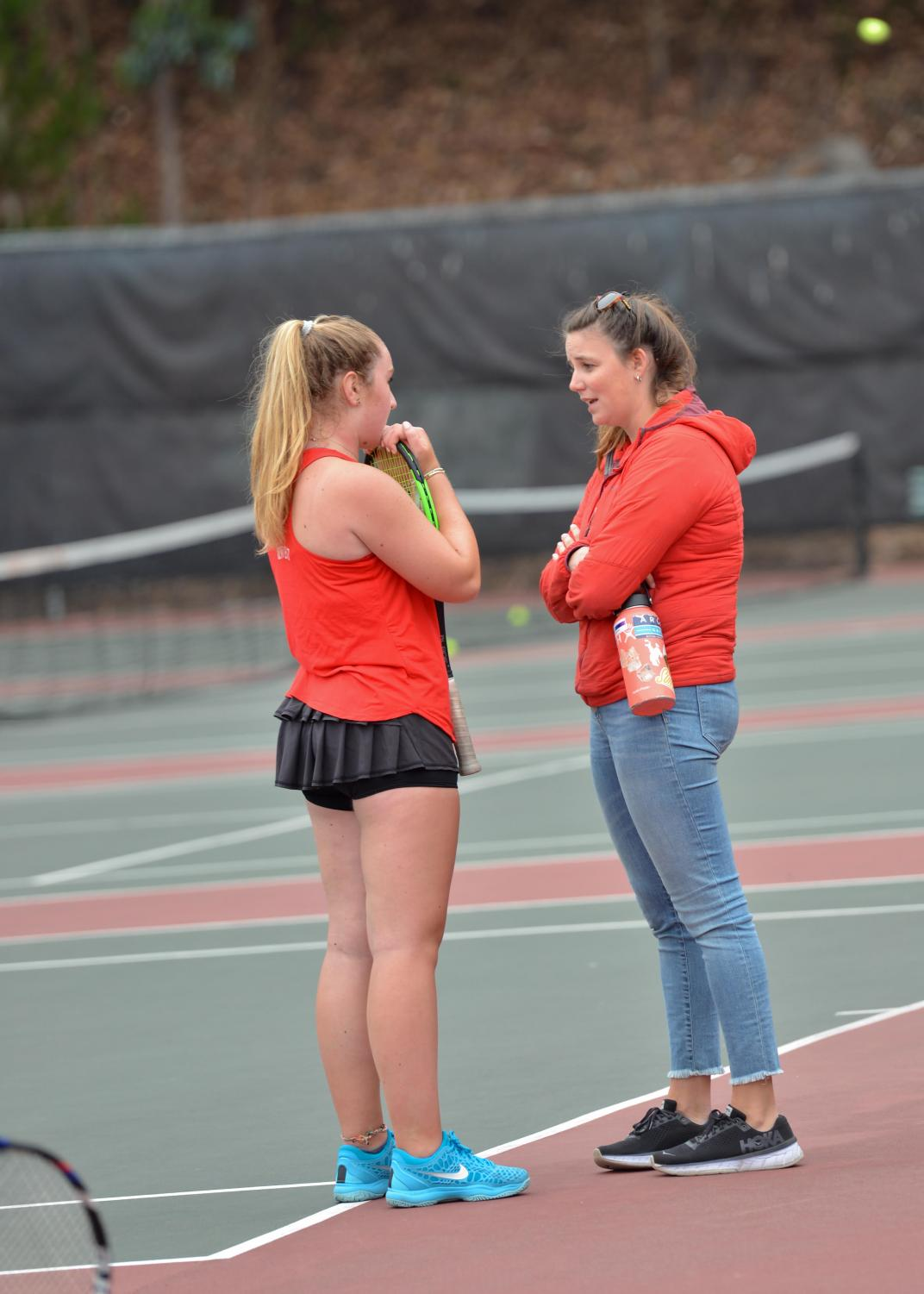 Varsity tennis coach Erin Minuth '11 chats with freshmen Elise Vulakh during a match against Sacred Heart Cathedral Preparatory. This is Minuth's first year as coach, and the team has a 5-0 record.