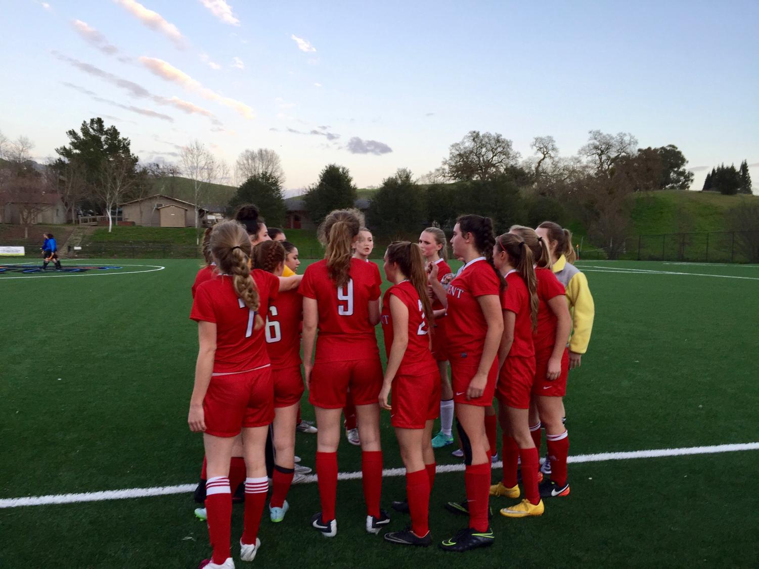 The soccer team huddles before a game last year. The season has been moved from spring to winter.