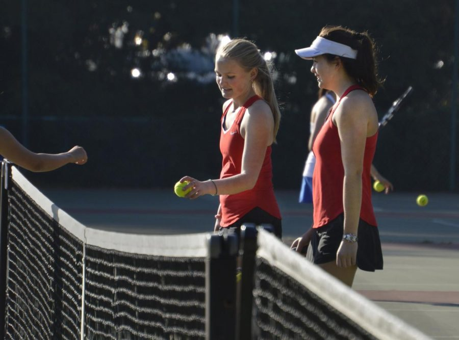 Seniors+Abby+Anderson+and+Mason+Cooney+hand+balls+to+their+opponents+at+the+end+of+a+game.+Both+seniors+have+played+tennis+for+Convent+since+freshman+year.+