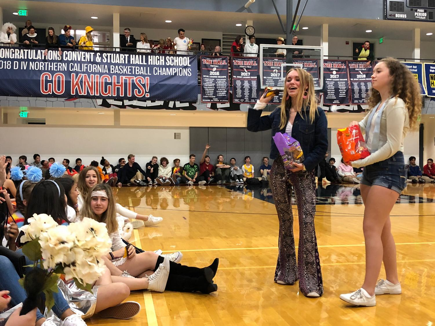Sophomore and freshman class representatives Tabitha Parent and Mackenna Moslander throw candy to students during the co-ed Halloween costume contest. The Convent & Stuart Hall student council led the assembly at the Pine/Octavia campus.