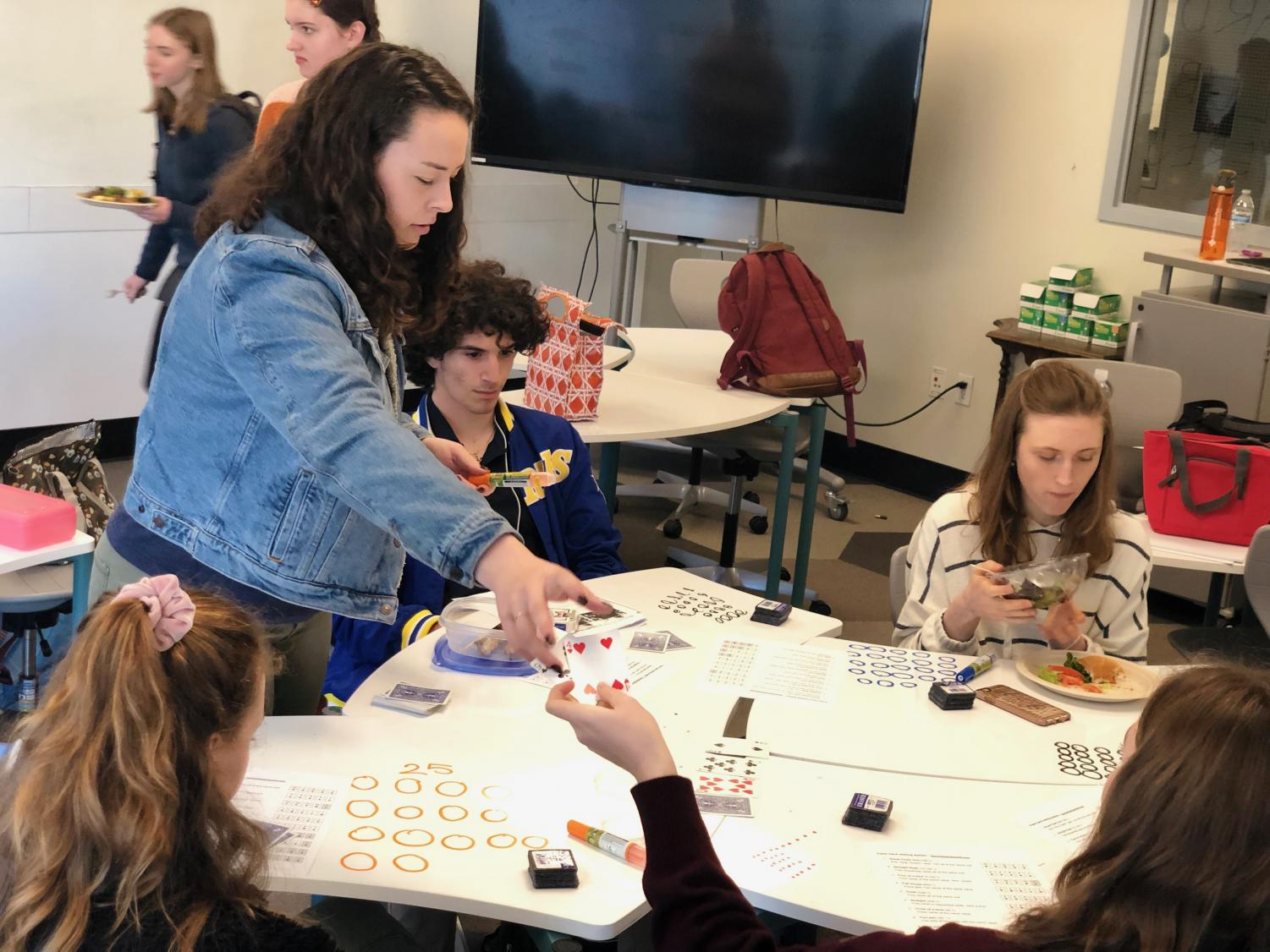 Card Club co-leader Dena Silver teaches members about Texas Hold'em Poker. First time poker player freshman Natalie Kushner aced the first round with a straight flush.