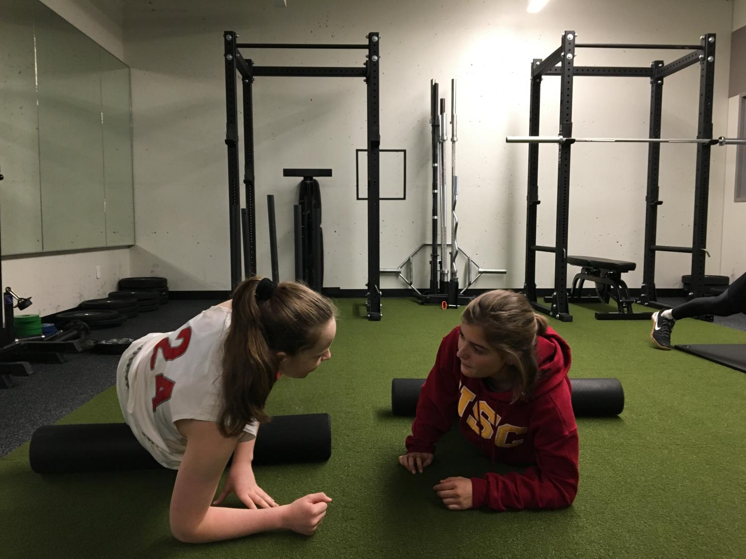 Sophomore Cecilia McQuaid and junior Sofia Telfer stretch in the weight room in the Herbert Center. The new mural will be painted on the back wall of this room.