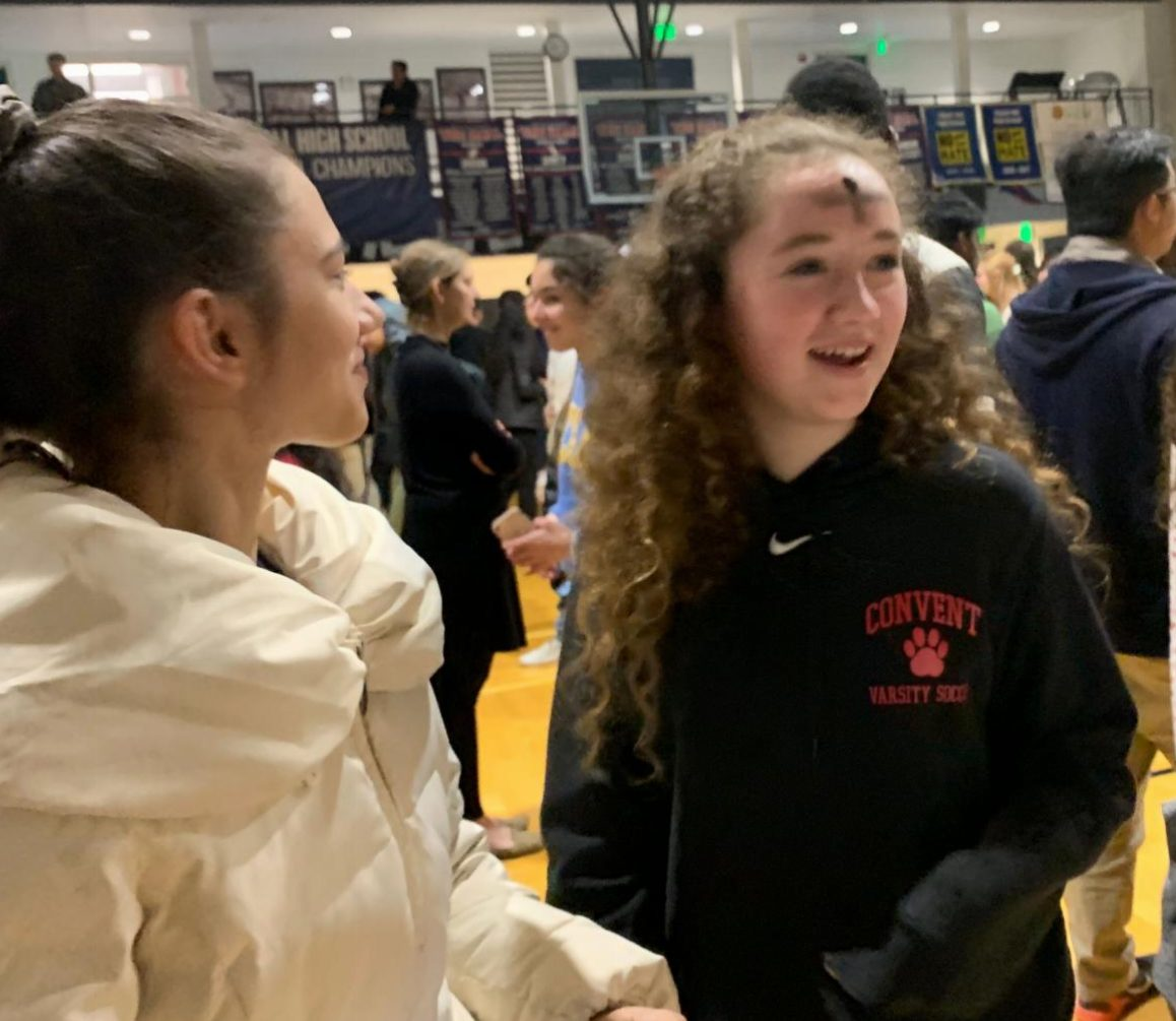Freshmen Lily Peta and Mackenna Moslander  walk back to their seats after receiving a cross on their foreheads during Ash Wednesday mass. Deacon Eddy blessed the ash before drawing crosses.