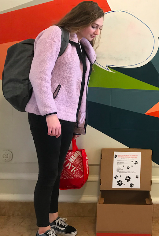 Sophomore+Ella+Holliday+donates+a+bag+of+supplies+for+the+%23AdoptDon%27tShop+drive.+Donation+bins+are+situated+in+multiple+locations+across+campus.+
