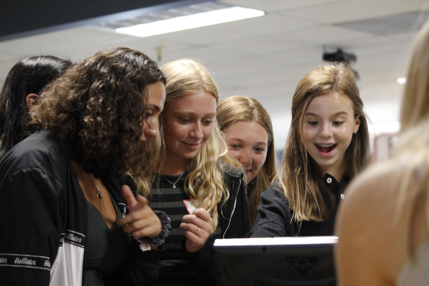 Freshmen Noor El-Qadah, Annika Hansen, Ella Noblin and Amaliya Sypult enter their names into the electronic scoreboard at Presidio Bowling Center on Aug. 16. Convent & Stuart Hall freshmen participated in arcade games, ate pizza and bowled.