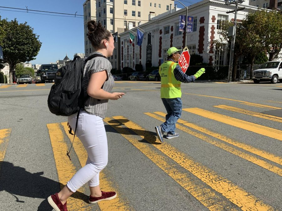 Senior+Dena+Silver+crosses+the+intersection+of+Broadway+and+Webster+streets+with+the+help+of+a+crossing+guard.+Traffic+commissioners+work+during+drop-off+and+pick-up+to+ensure+safety.