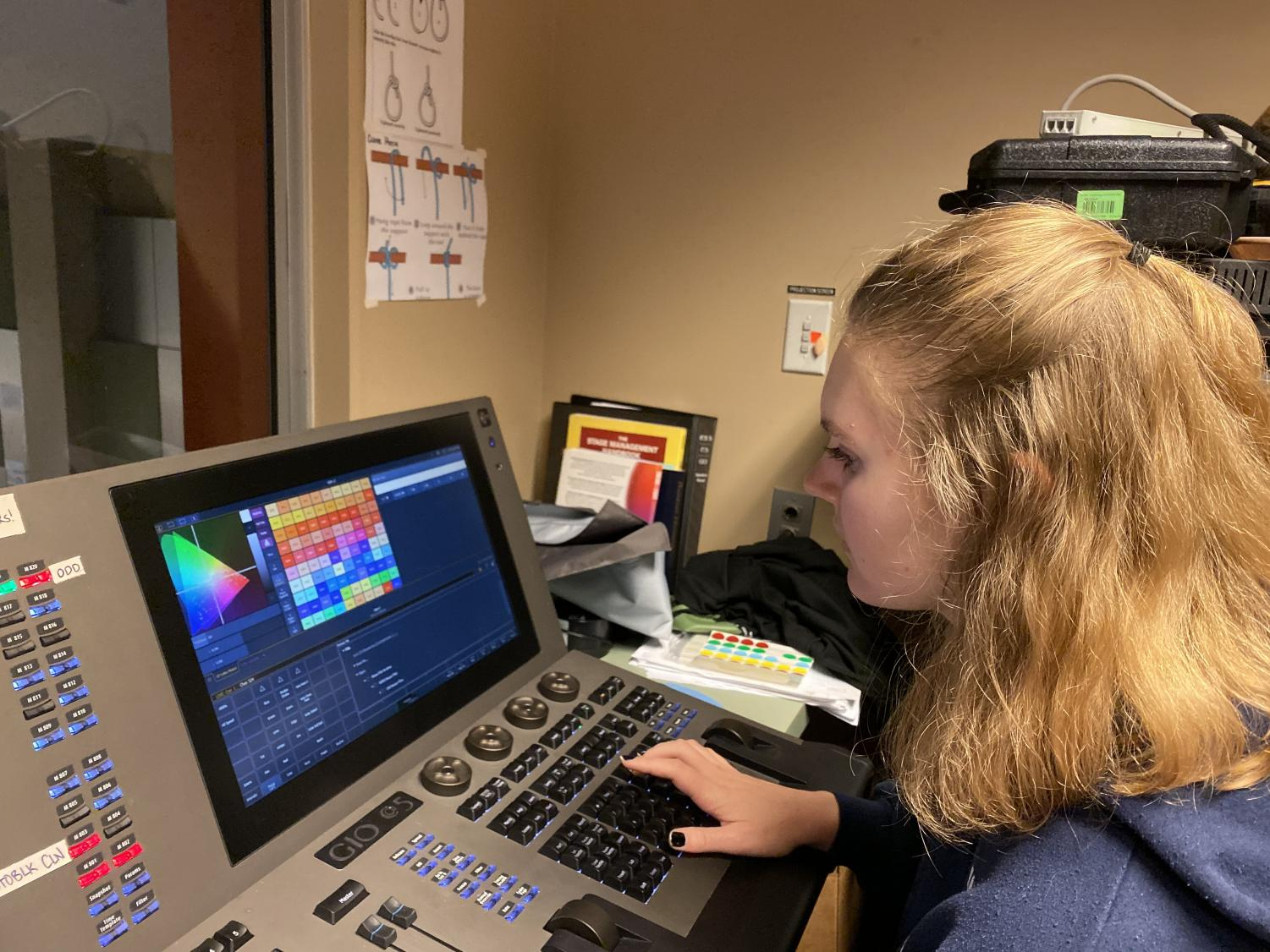 Lighting designer Amy Phipps works on lighting cues for the fall play during tech week. Phipps has spent two months working on lighting design for the production.