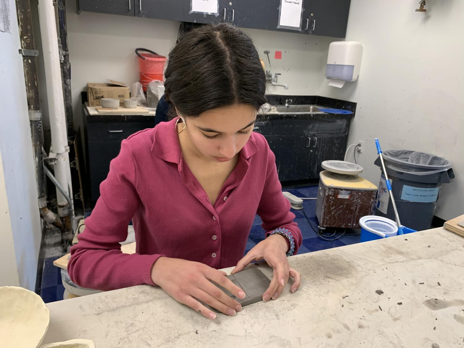 Sophomore Haya Jadallah creates a domino out of clay for her project that represents the domino effect of the contamination of the ocean. This Art Foundation II project pushes students to reflect the environment around them in their work.