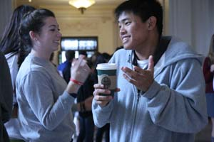 Nate Tom, SHHS Student Body President, chats with sophomore Kendall Scullion at Breakfast Club last Thursday morning. Students from both schools gathered in the Main Hall exchanging hugs and quick greetings before faculty herded them up the Marble Stairs to the Center where a few boys sold donuts and students chatted and listened to music.