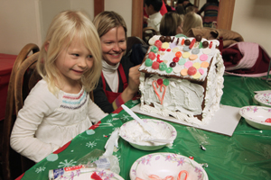 A gingerbread house builder inspects her project for spots that could use more frosting or candy at the annual Gingerbread Workshop. Parents and high school student volunteers kept the kids stocked with supplies — M&M's, sour gummi belts, jelly beans, gum drops, candy canes and other sugary treats for house decorating.     KATHERINE MIBELLI | the broadview