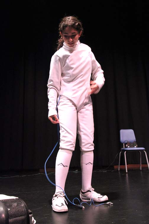 Senior Beth Levin demonstrates putting on her fencing gear before a mock bout at Principal's Meeting on Monday.